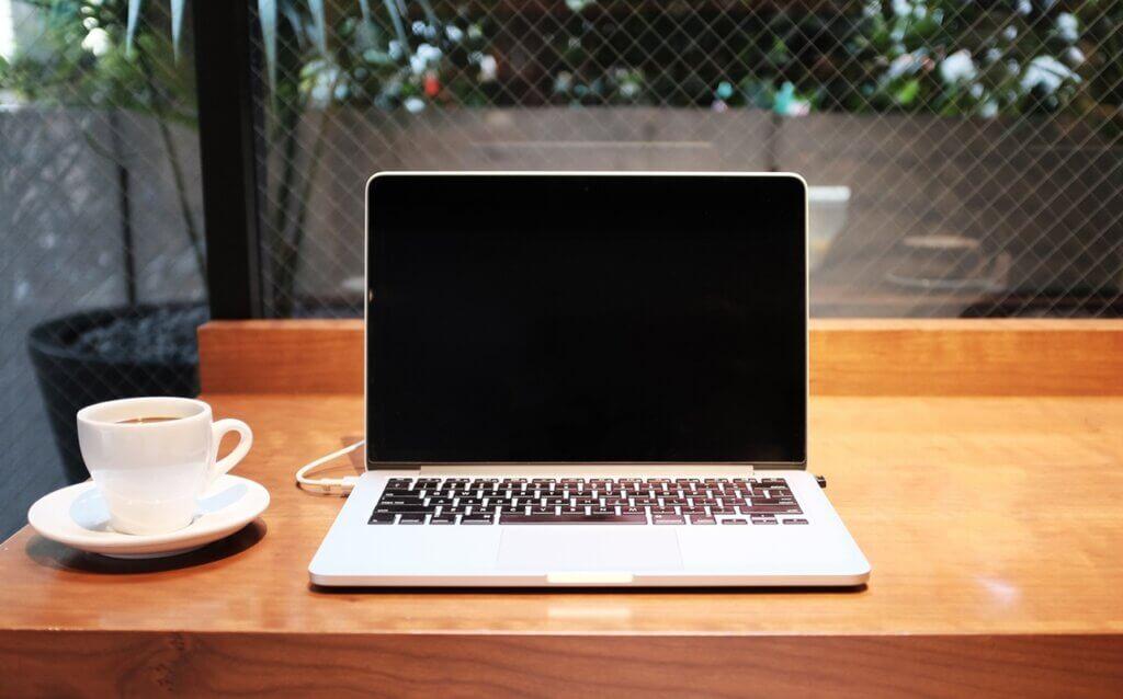 電源の切れたパソコンとコーヒーの画像
